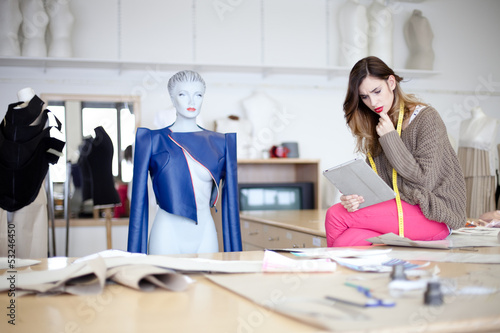 Fashion designer looking at designs on tablet computer. In the s