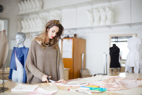 Fashion designer cutting fabric textile in a studio