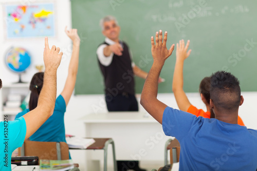 high school students with hands up in classroom