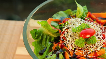 Bowl of fresh vegetable salad with dressing - dolly shot