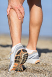 Sport injury - Man running clutching calf muscle