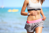 Fototapety Runner woman with heart rate monitor running
