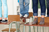 teen students standing on school desks