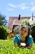 junge Frau liegt auf Rasen und ißt Apfel