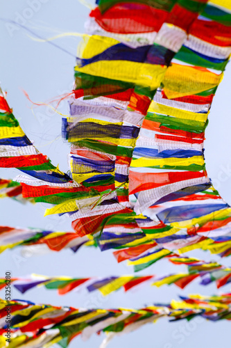 Buddhist Tibetan prayer flags against blue sky background