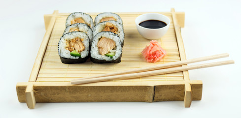 Chicken maki rolls with soy sauce on a rustic bamboo mat