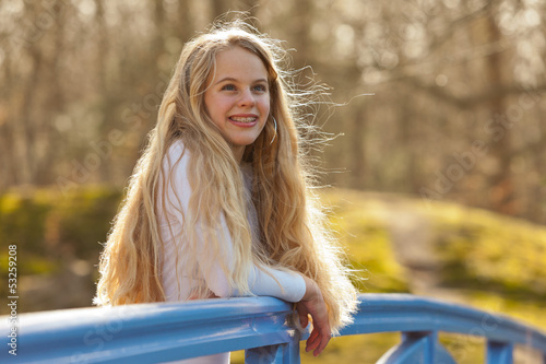 Happy young girl with long blonde hair on bridge in park.