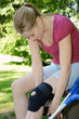 Junge Frau legt Kniebandage an