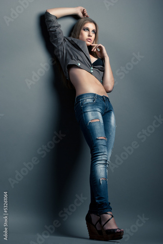 Young sensual woman in jeans over grey