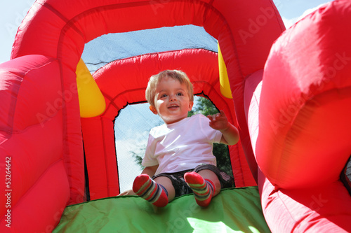 Child on bouncy castle slide