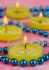 Lighted candles with beads on pink background