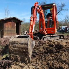 Ein junger Bauarbeiter gräbt in der Erde