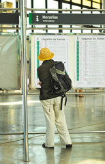 Mujer en la estación mirando horarios de tren