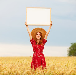 Redhead girl with blackboard at wheat field