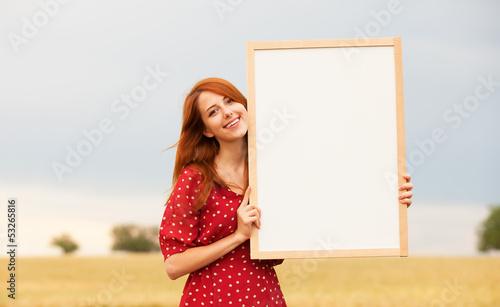Redhead girl with blackboard at wheat field