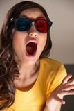 Expressive young woman watching 3d film