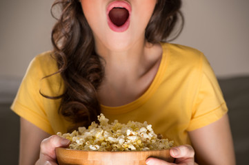 Unrecognizable woman eating popcorn at the cinema