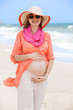 Beautiful pregnant woman at the beach looking happy