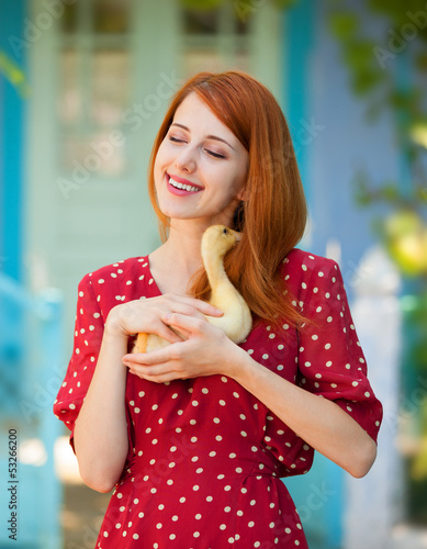 Redhead girl with duck near old house