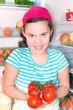 Mädchen hlt Tomaten aus dem geöffneten Kühlschrank