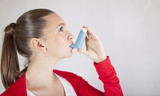 Cute girl using an asthma inhaler for preventing attacks