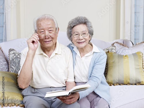 senior asian couple holding a book and smiling