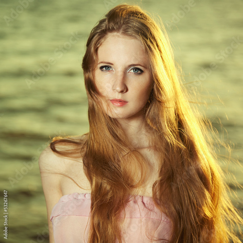 Beautiful redhead girl at pond