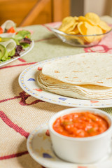 Traditional mexican food with a plate of tortillas, fresh salad,
