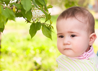 Thoughtful child near a blossoming cherry