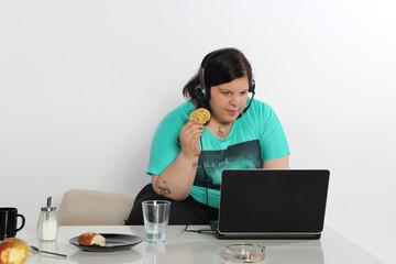 junge Frau isst vor dem PC