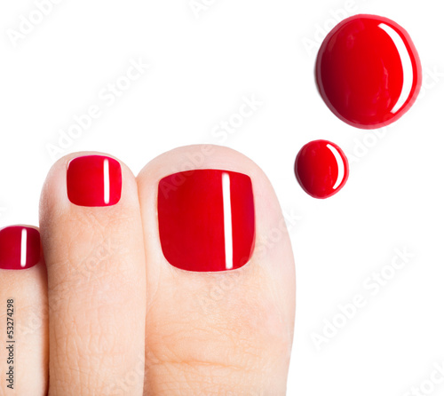 Beautiful female toes with red pedicure and drops of nail polish