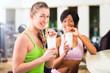 women in the gym drinking protein shake