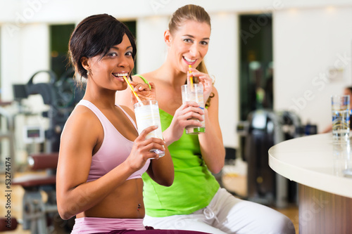 women in the gym drinking protein shake