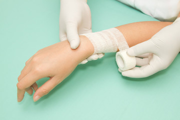 Doctor 's hands wrapping a bandage on forearm