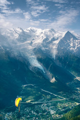 Yellow paraglide over Alps green valley