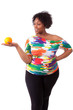 Overweight young black woman holding an orange - African people