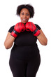 Overweight young black woman holding boxing gloves - African peo