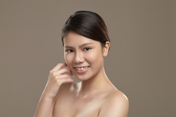 A female asian with natural make up is smiling to the camera
