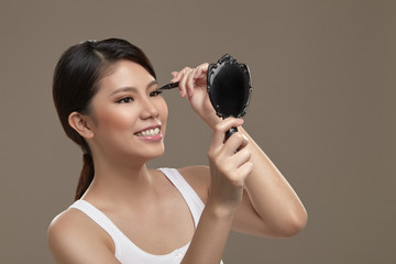 Female asian applying eye liner with mirror