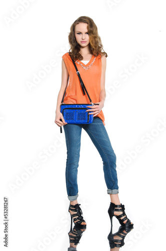 Full body young woman in shirt and bag posing at studio