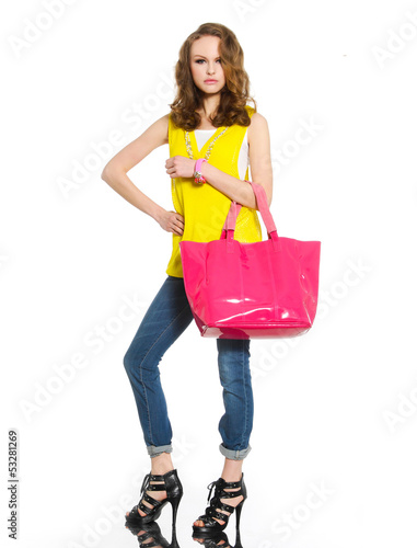 Full body young woman in shirt and red bag posing at studio