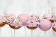 Pink cake pops on white wooden background. Copy space