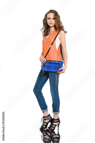Full body young woman in shirt and blue bag posing at studio