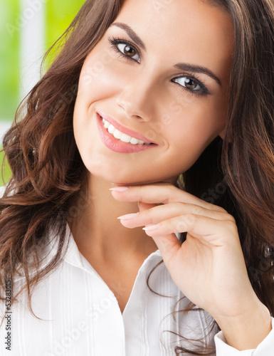 Portrait of thinking cheerful businesswoman