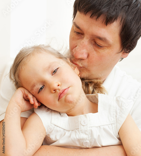 Father comforts a sad girl