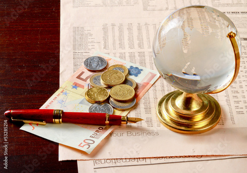 Globe and money euro isolation on wood background