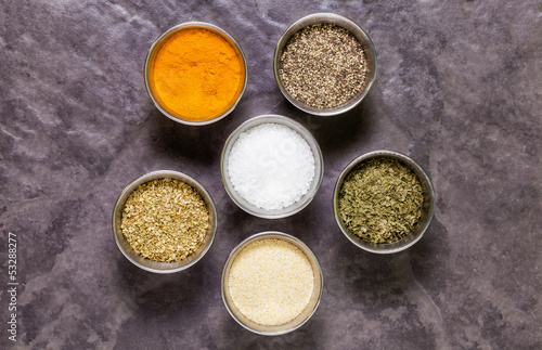 Herbs and spices in round pots on slate tile