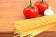 uncooked spaghetti, garlic and tomatos on a preparation board