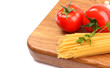 uncooked spaghetti, garlic and tomatos on a board