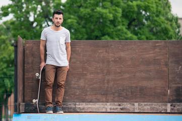 Skateboarder portrait standing on halfpipe at skatepark.